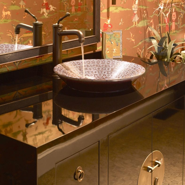 Blue printed basin with brass faucet atop a black vanity