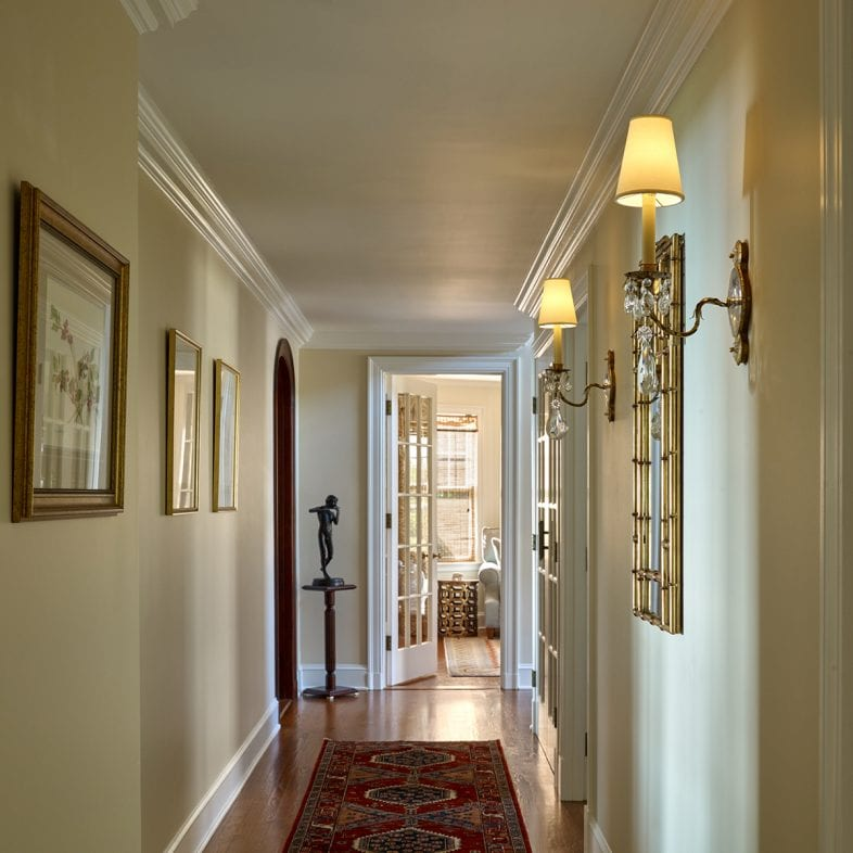 The hallway with unique sconces and red hued rug details.