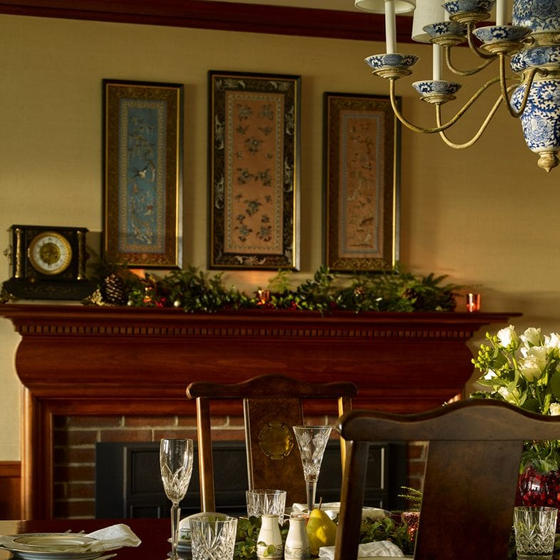 Formal dining room with a brick fireplace, vintage clock, and large table.