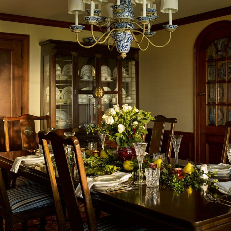 Large formal dining room with large china cabinet, built-in fine china cabinet, elegant chandelier, and spacious dining table.