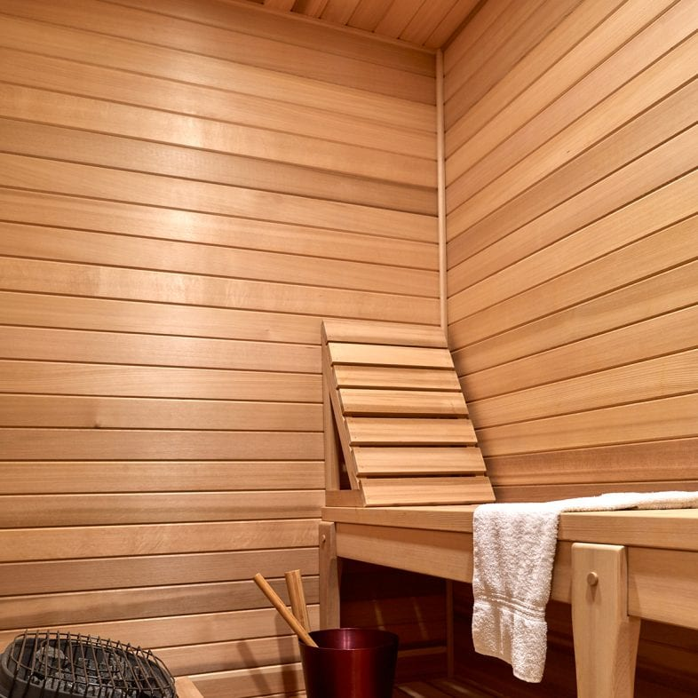 A sauna with bench and backrest for comfort.