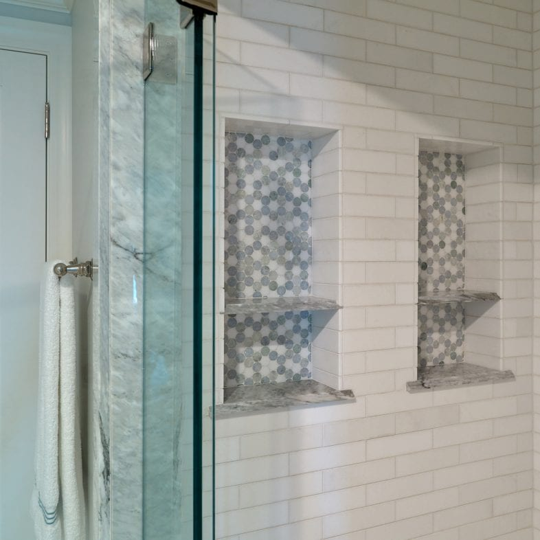 A large walk-in tiled shower with built-in shelves and marble accents.