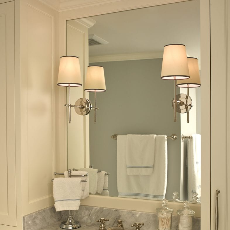 An ivory vanity with gray marbled countertop and large mirror.