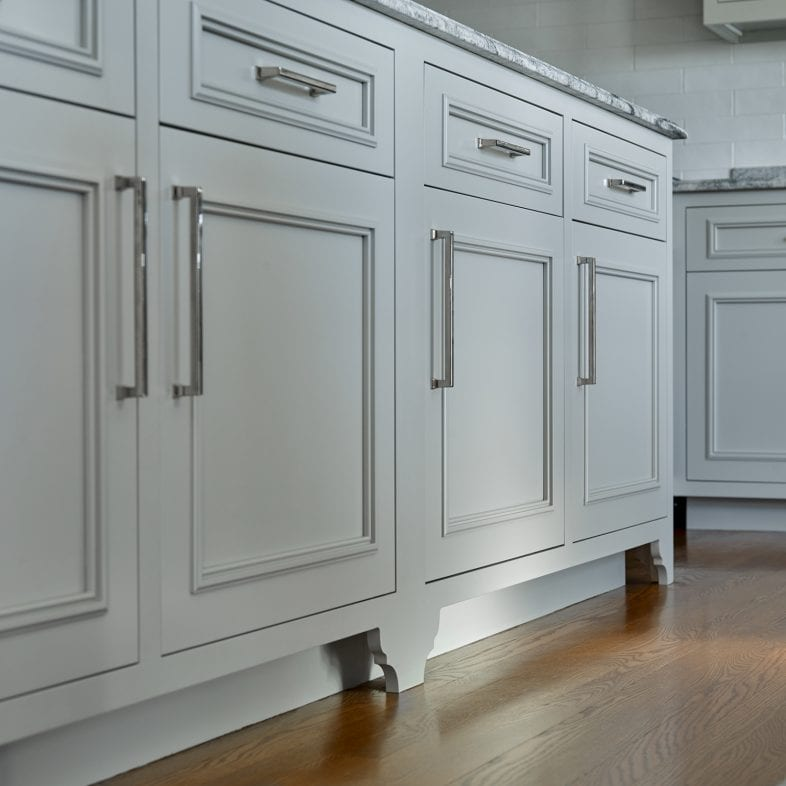 A close-up of the detailed trim of the cupboard and island in the kitchen.