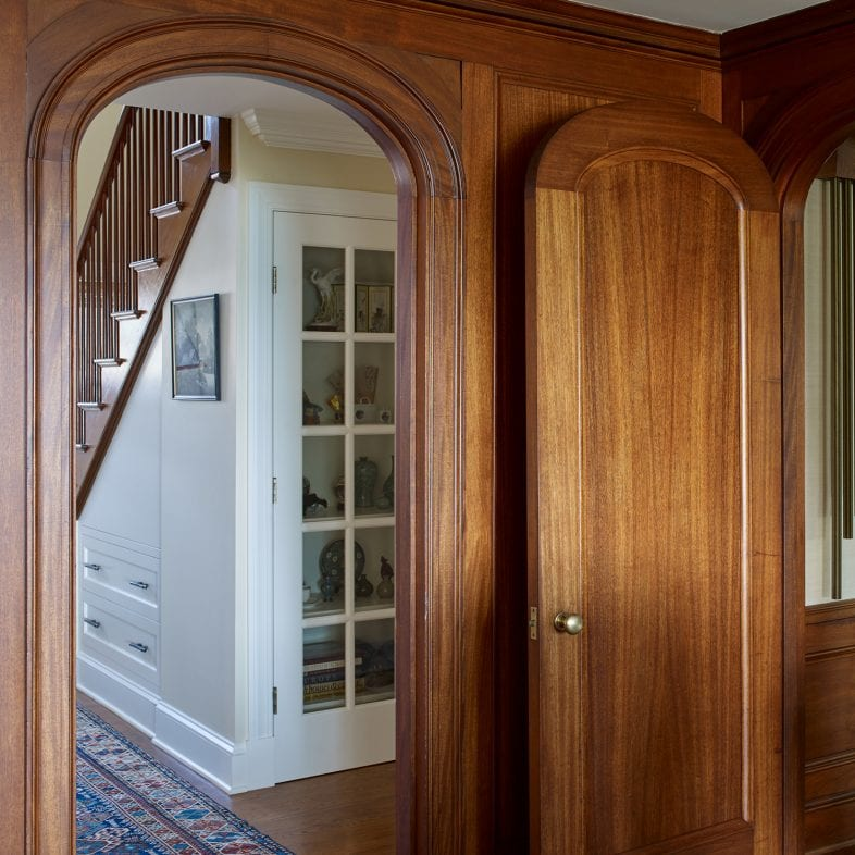 Rounded doorways with views of the built-in bookshelf with glass door.