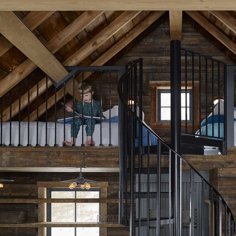 Spiral iron stair leads to loft with two beds and exposed beams.