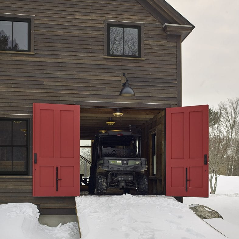 The cozy barn-style home has large doors for storing toys and staying out of the snow.