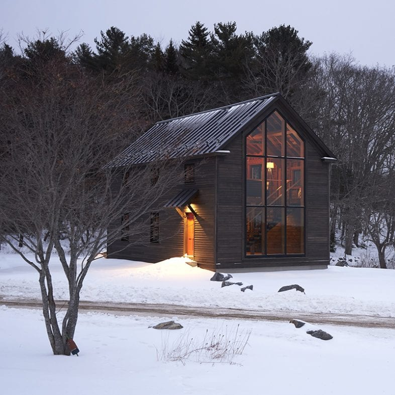 The approach to the cozy barn-style retreat with large picture windows