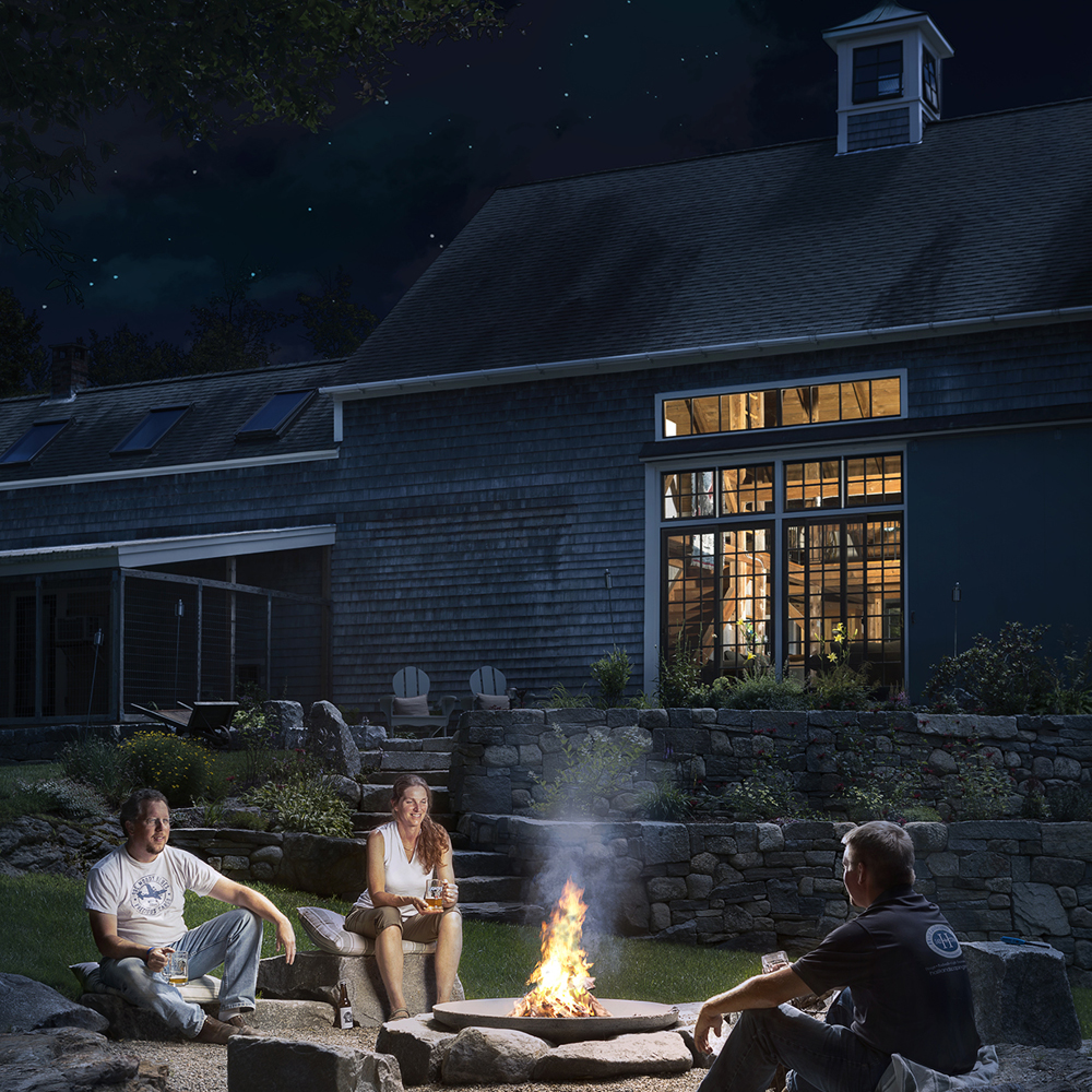 Exterior evening capture of this beautiful barn-style home with multi-level rock walls and nature inspired firepit.