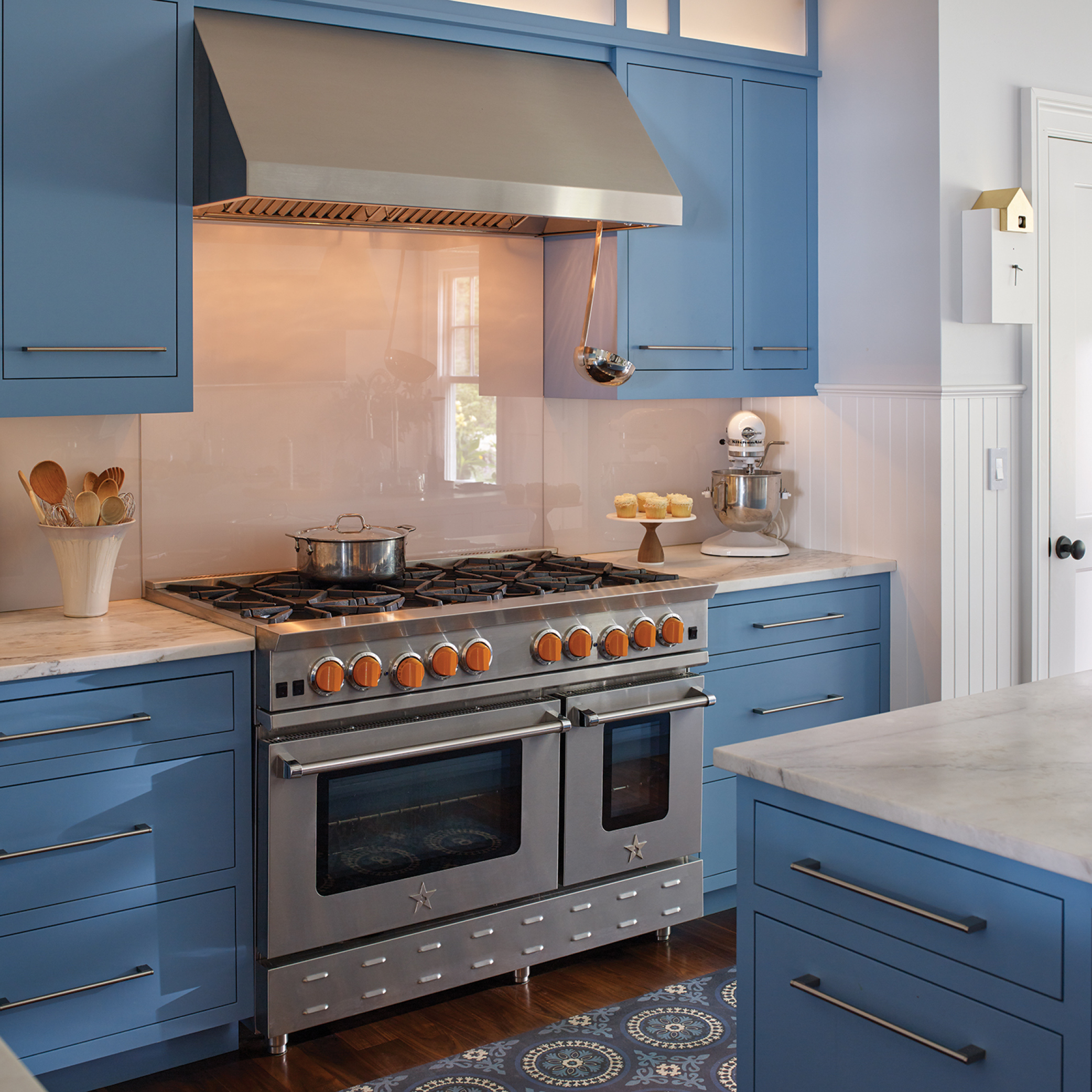 Large double oven with vent, blue cabinets, and marble countertops. Summer Haven.
