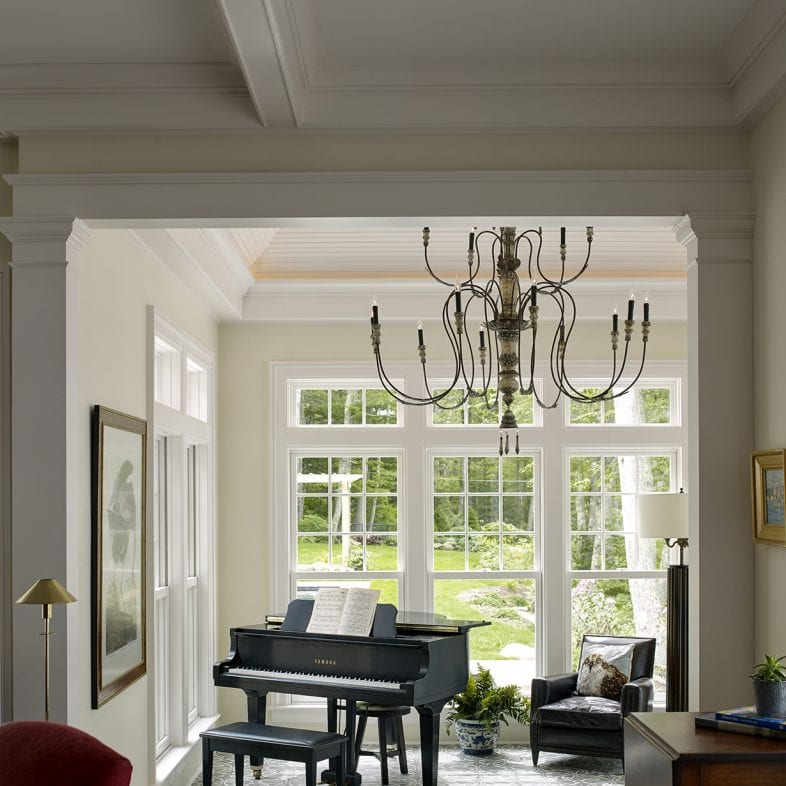 Grand piano with large picture windows and iron chandelier