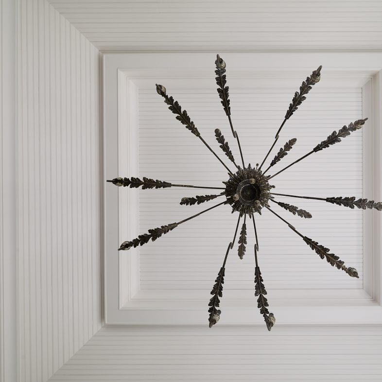 A unique metal feathered chandelier with white shiplap ceiling
