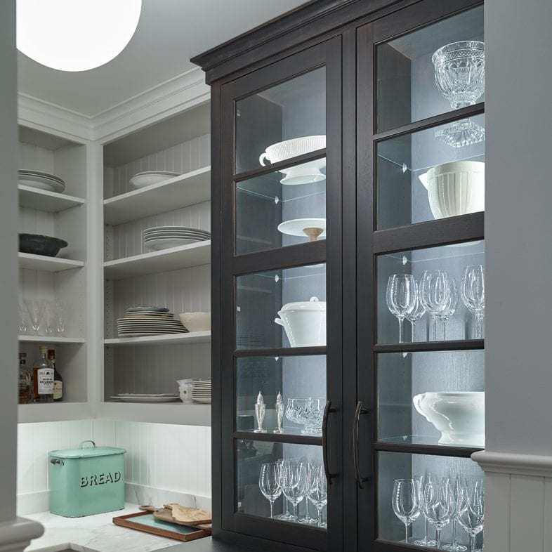 A dark hutch for storing glassware in the pantry, with white and marble accents throughout