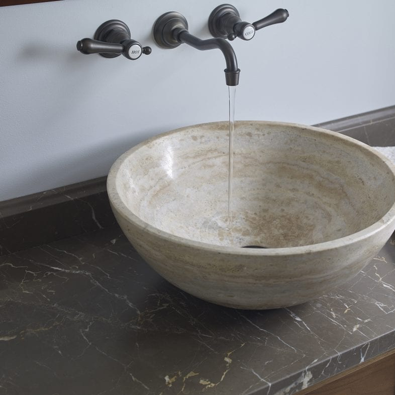 Unique stone basin with brass faucet and black marble countertop.