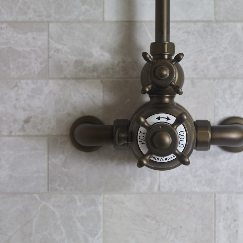 Vintage shower faucet with brass coloring and marble tiled walls.
