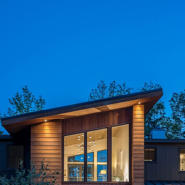The evening approach with focus on wood paneled siding and large picture windows.