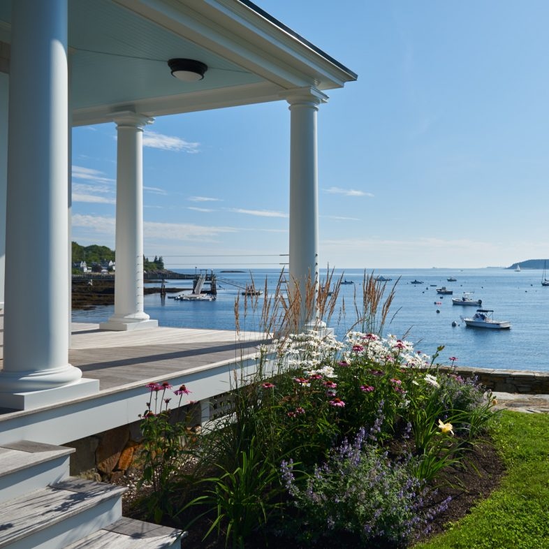 Coastal views from Twin Cove property with stone wall details and flower gardens along the wrap porch.