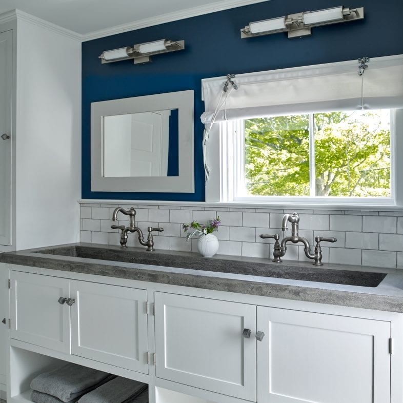 Greys, white, and navy blue colors tie this bathroom together with the trough sink and storage area.
