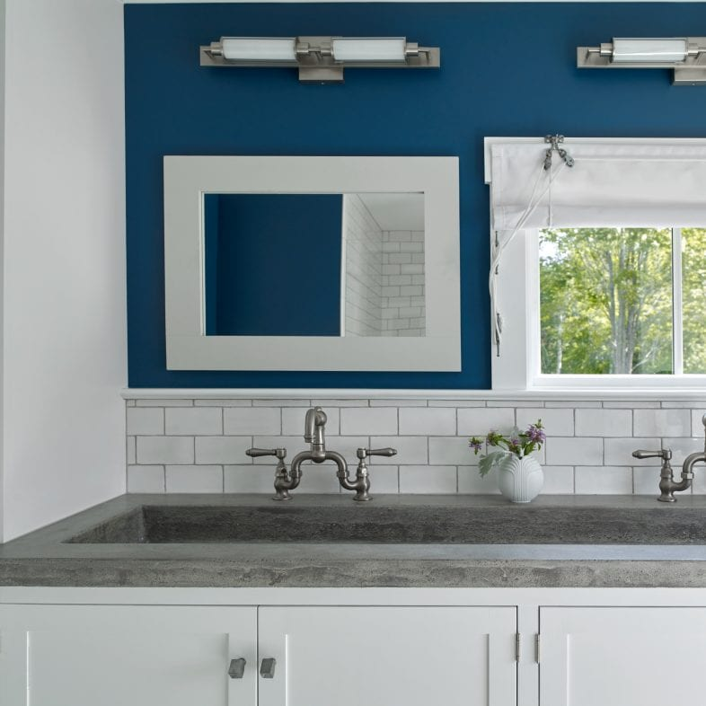 Double trough sink with beautiful contrast and navy blue accent wall.