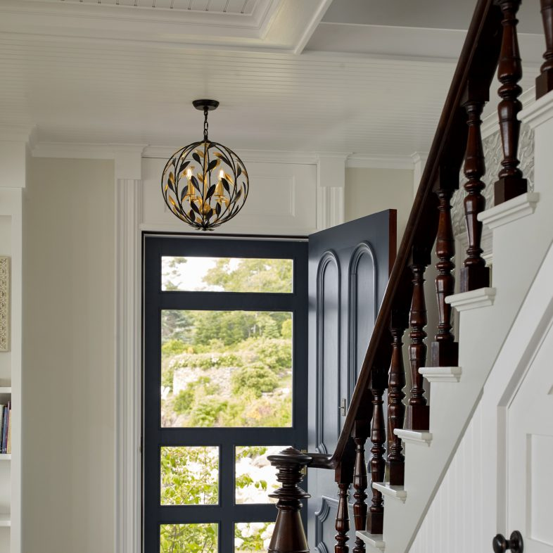Beautiful staircase to entryway which features a unique light fixture, tile and wood flooring, and stunning contrast.