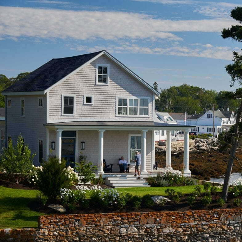 Welcoming view of coastal Maine home with flag, stone wall, classic pillars, a wrap porch, and beautiful floral accent along the ocean.