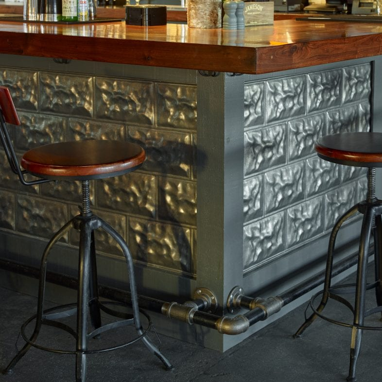 Industrial style bar area with pipe and metal finishings.