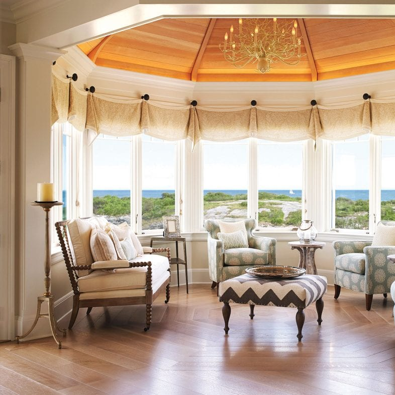 Large bright greet room with gold chandelier and 180 degrees of coastal views.
