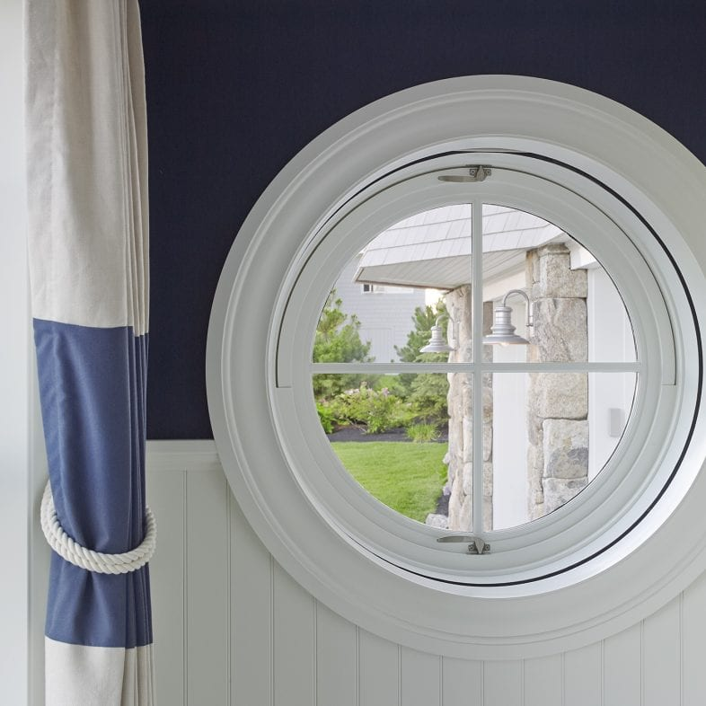 A circular window with views of the ocean and yard.