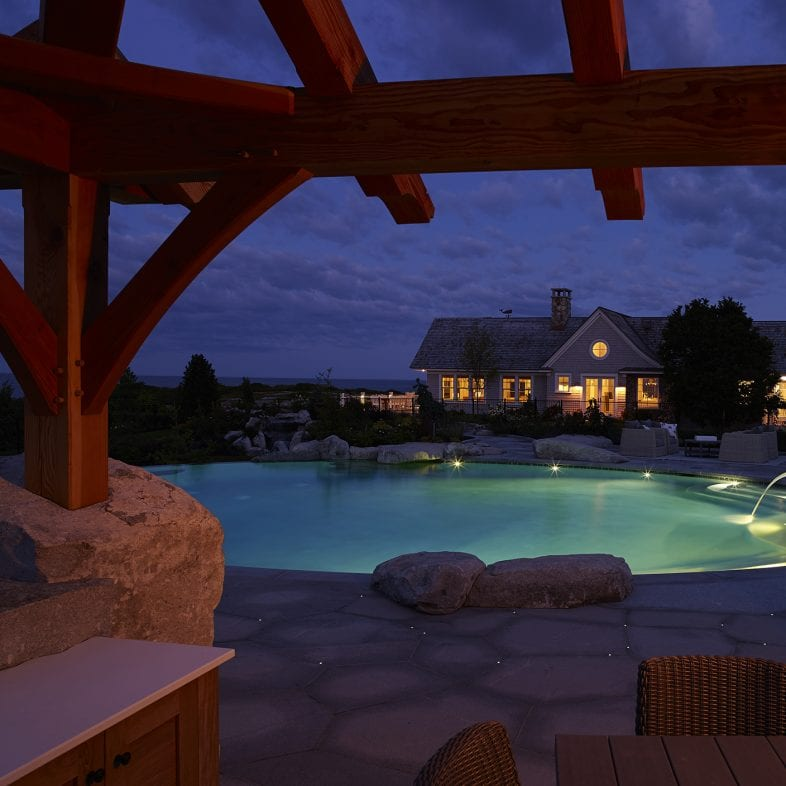 Evening view of Whales Watch and the inground hot tub and pool from the pergola