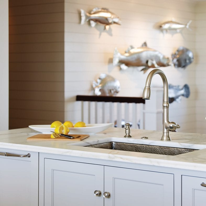 A view of the white marble countertop with hammer finished sink and steel decorative fish in the background.