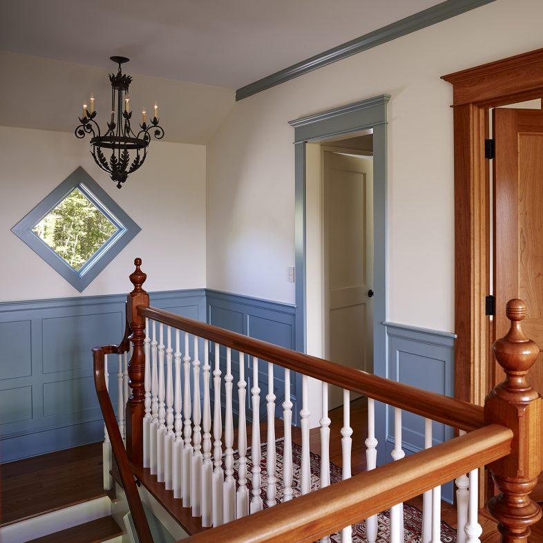 Upstairs hall with blue wainscoting and wooden door at Highfields