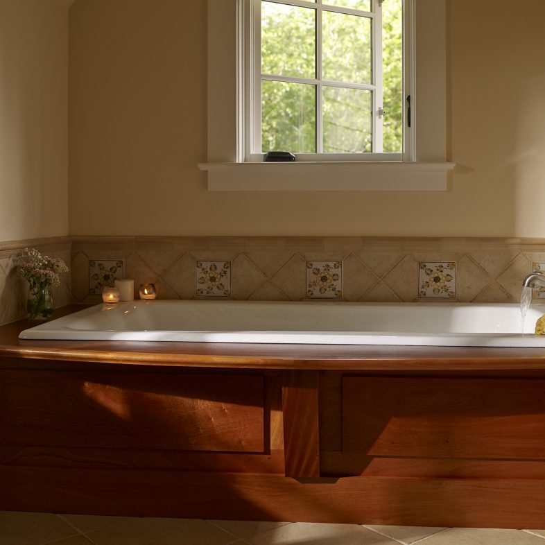 Large soaking tub with a window in the bathroom at Highfields