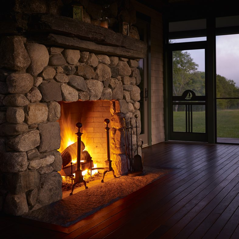 Cozy stone fireplace at night with water views at Highfields