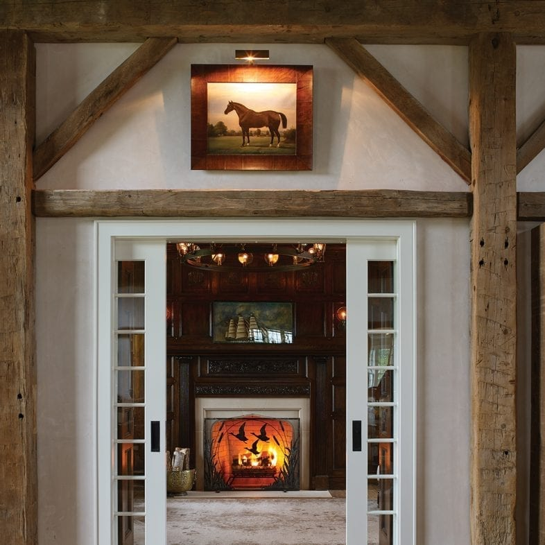 This rustic entry to the den is complete with the horse painting and open wooden beams.