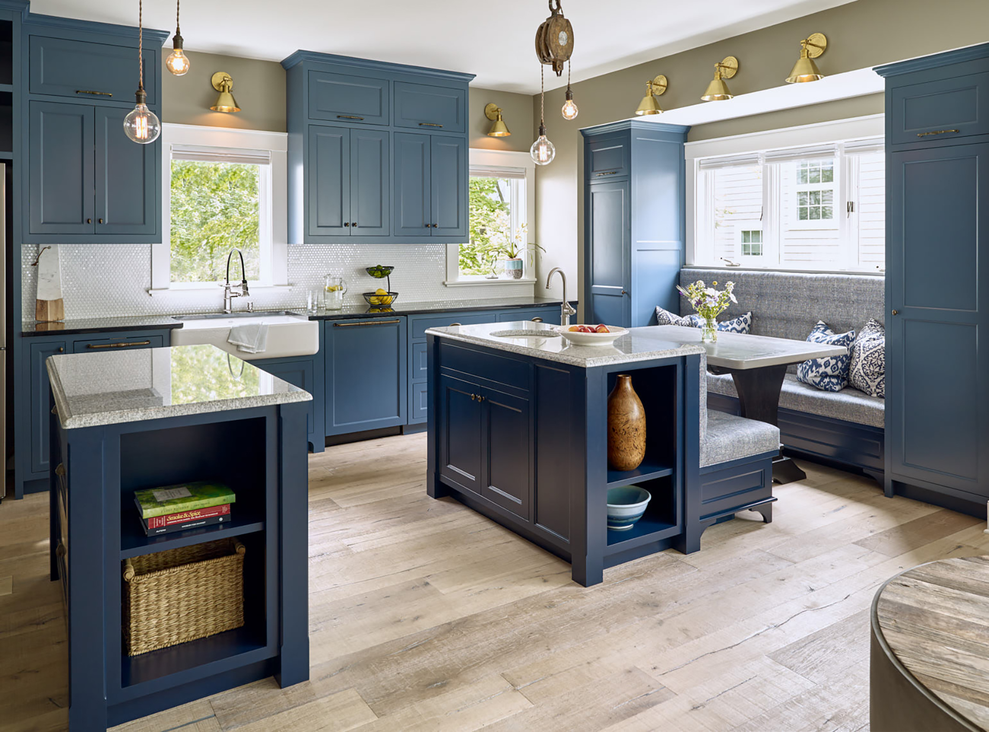 Large blue kitchen with built-in bench sitting areas and unique vintage lighting.