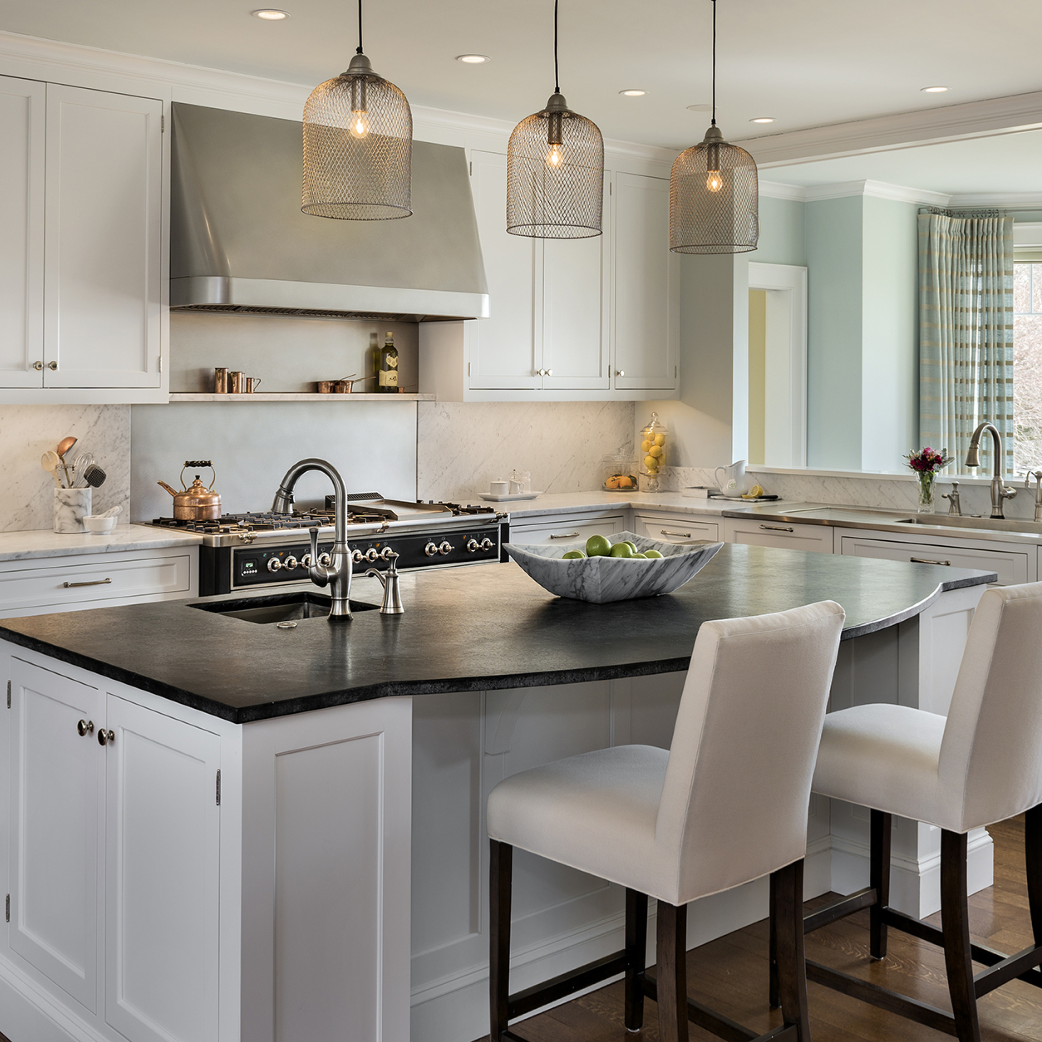 A large and bright kitchen in Cumberland Foreside with unique sconces, and marble countertops