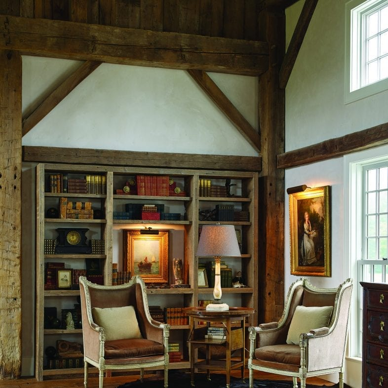 Rustic library space with wooden beams and unique throw rugs.