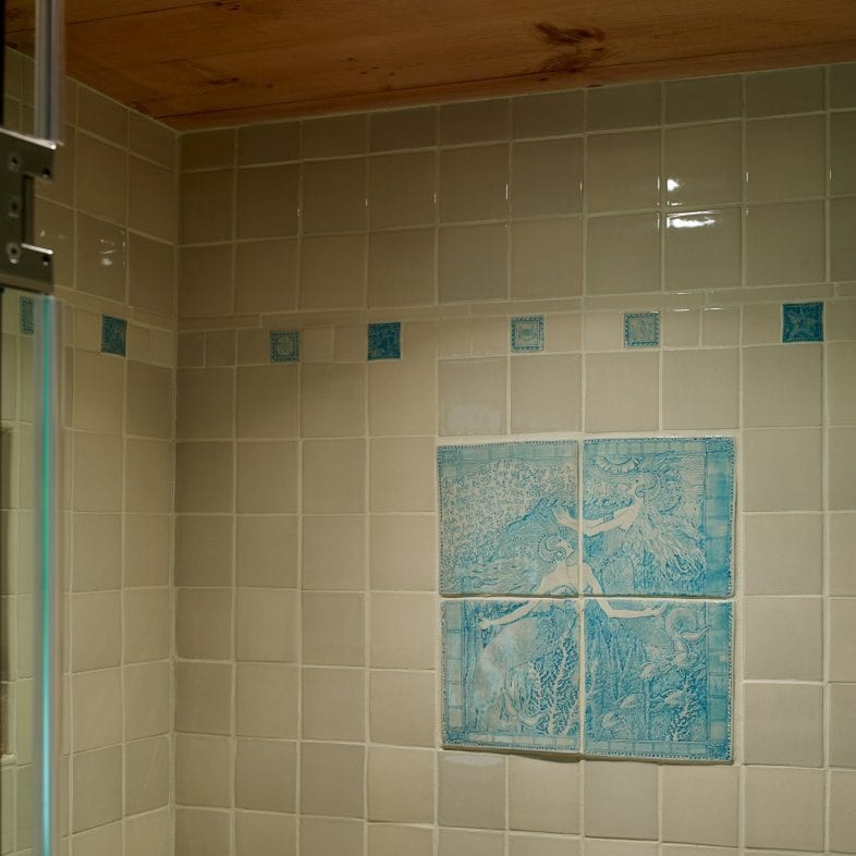 Decorative tiles in the shower at Little Acorn Cottage