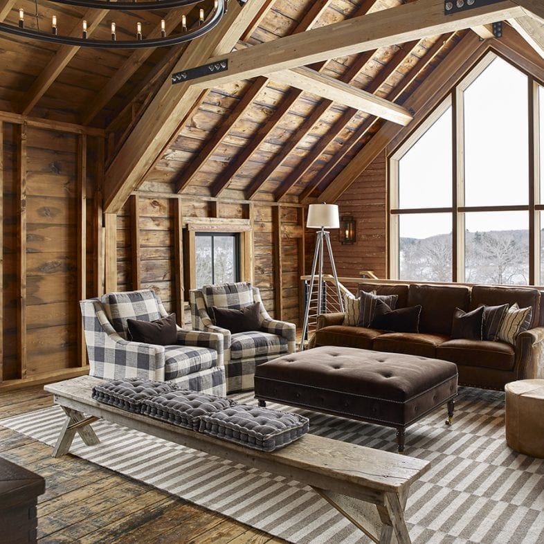 Cozy, rustic, and spacious living room with large picture windows and exposed beam.