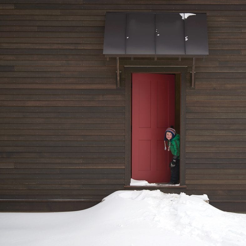 This welcoming red door couples well with the dark stain on this barn-style spa area.