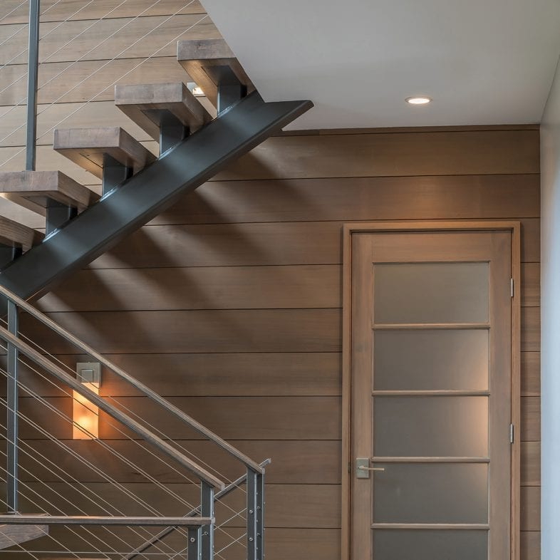 The contemporary staircase with the cabin-style paneled wall