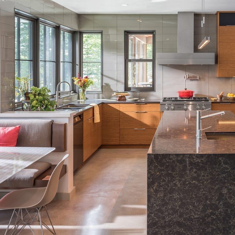 A large contemporary kitchen with a lot of cabinet space and granite island