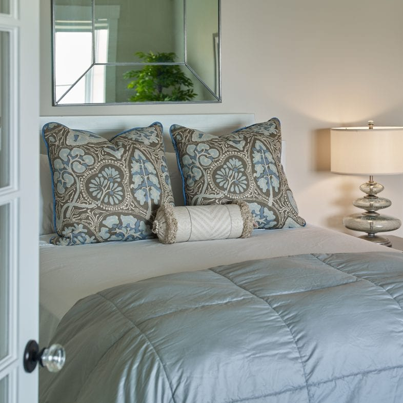 A guest bedroom with unique lamp, blue hue themes, and coastal views at Umami Point
