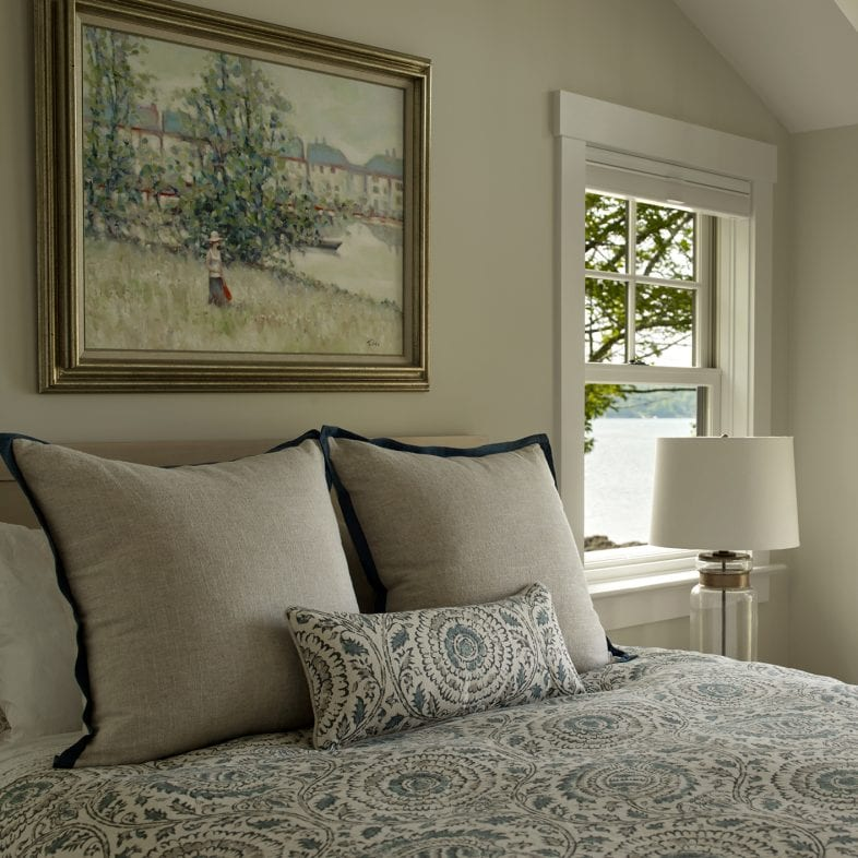 Bright guesthouse bedroom with blue accents, art, coastal views, and porch access at Umami Point.