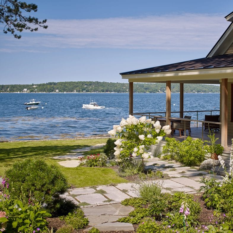 The wrap around porch with stone walkways, flower gardens, and coastal views at Umami Point.