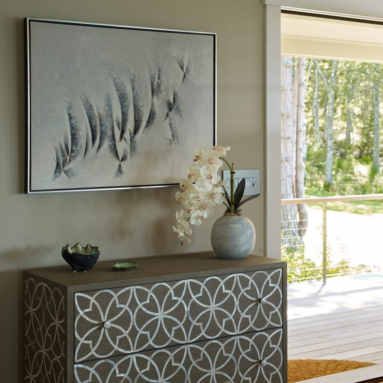 A dresser with silver design on wood along the entryway.