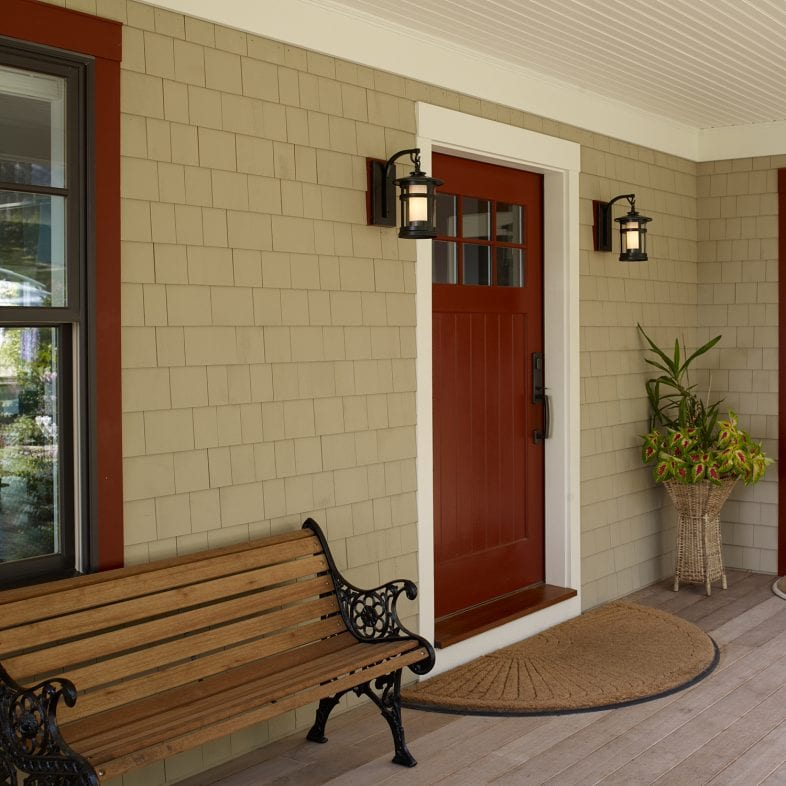 Front doors with lantern-style outside lights, warm welcoming doors with windows at the top, and a bench on the front porch.