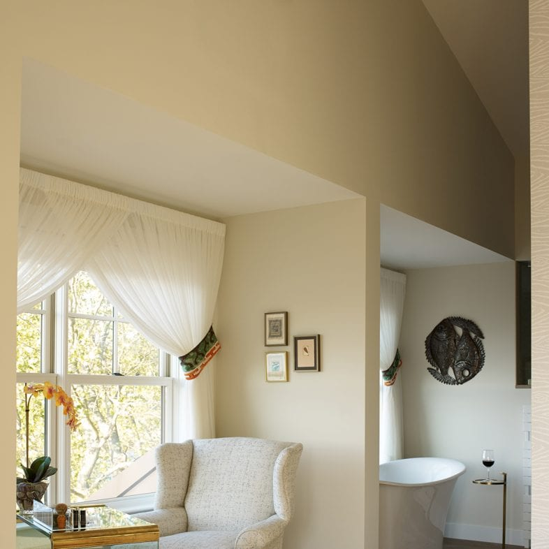 A spa room with clawfoot chair and bathtub, both with coastal views